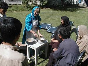 Grace Magney demonstrating solar cooking in Afghanistan