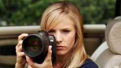 A promotional photo of Veronica Mars doing some surveillance.