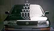 Car front view, halfway lit, with 15 champagne glasses stacked on the hood to form a triangle.